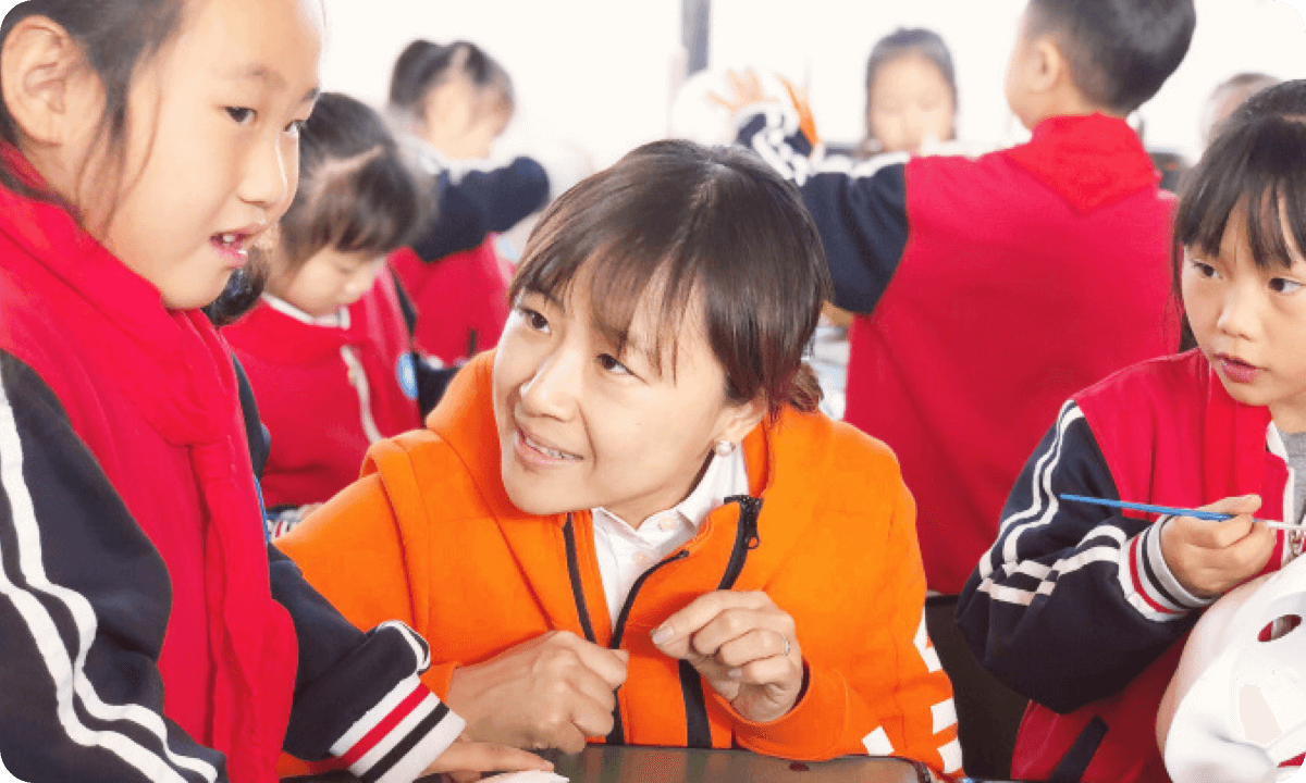 VIPKid CEO Cindy Mi working with students in the classroom in China